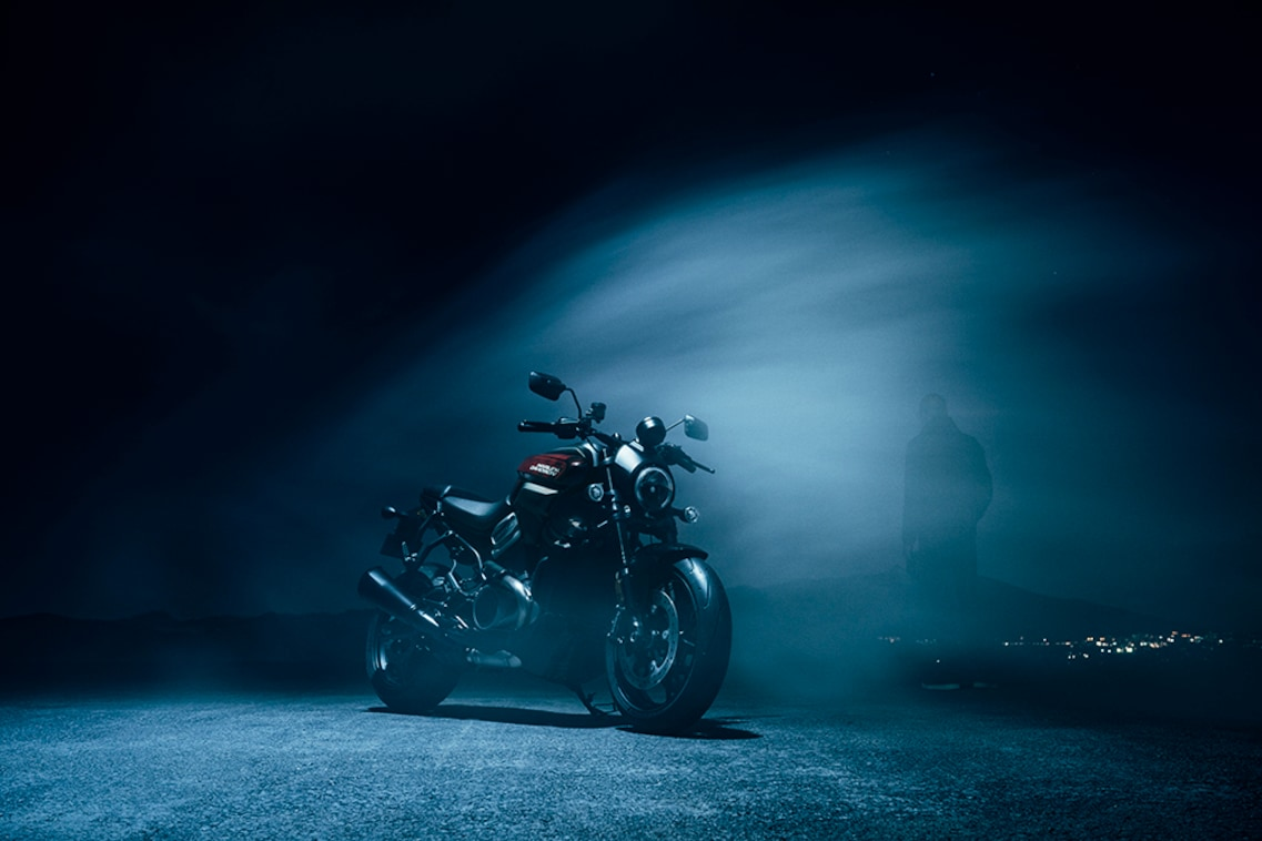 A Harley Davidson Bronx sits in a darkened parking lot.