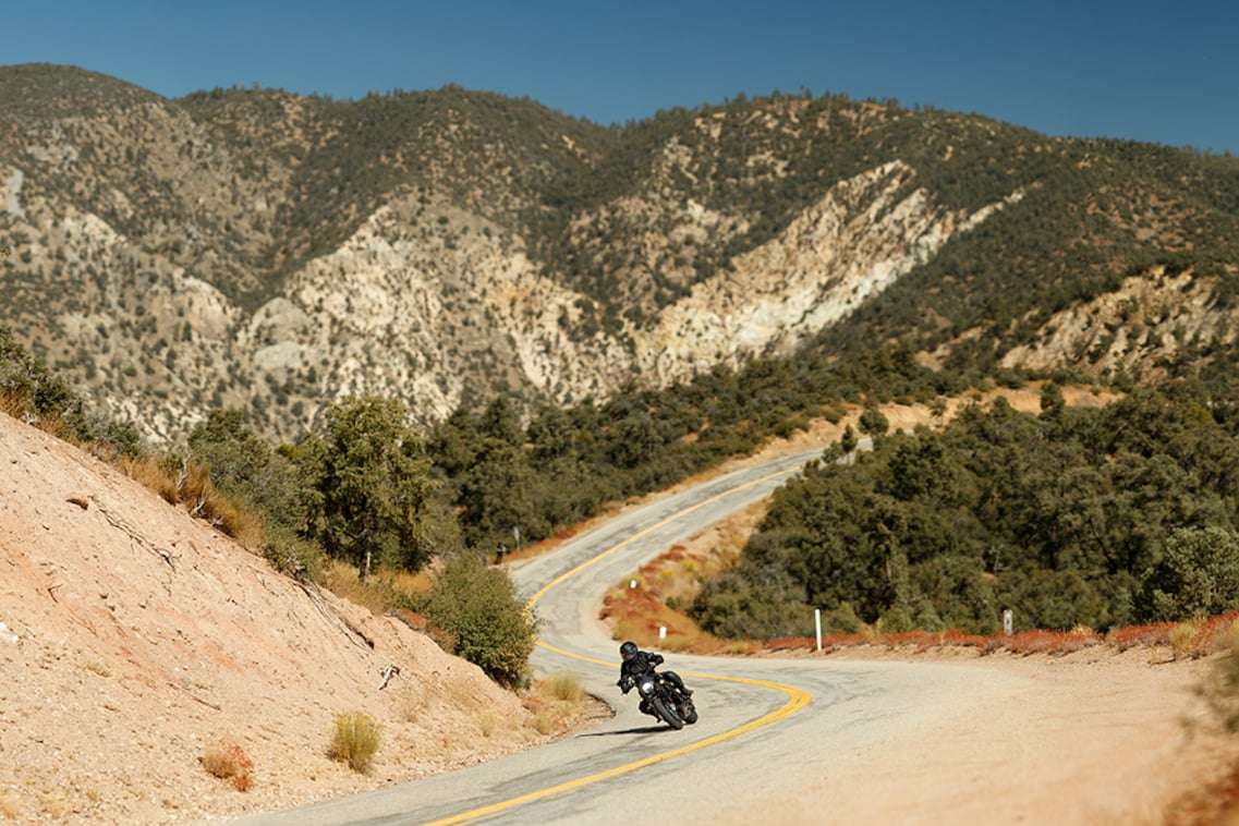 A Harley-Davidson Bronx soars around a mountain road.