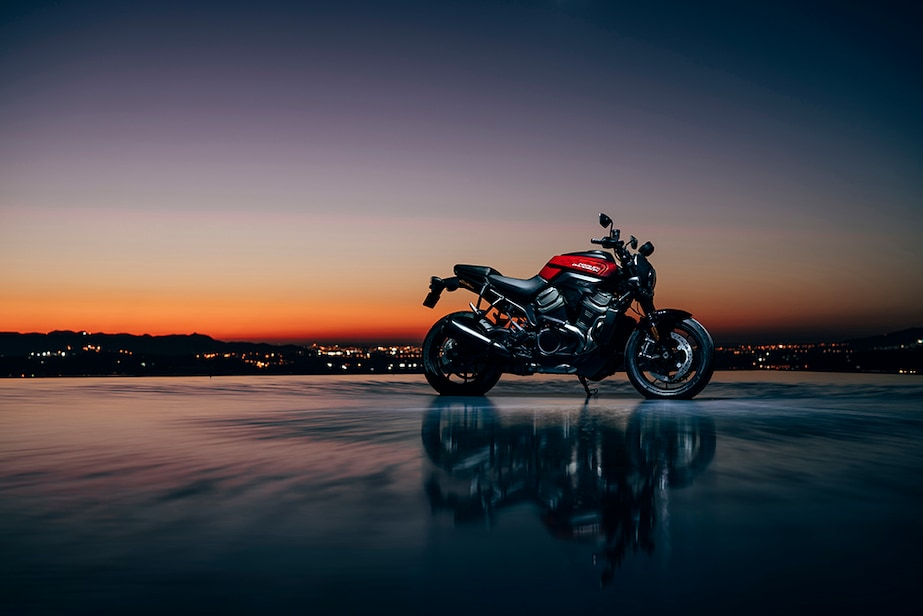The sun sets behind a red Harley-Davidson Bronx.