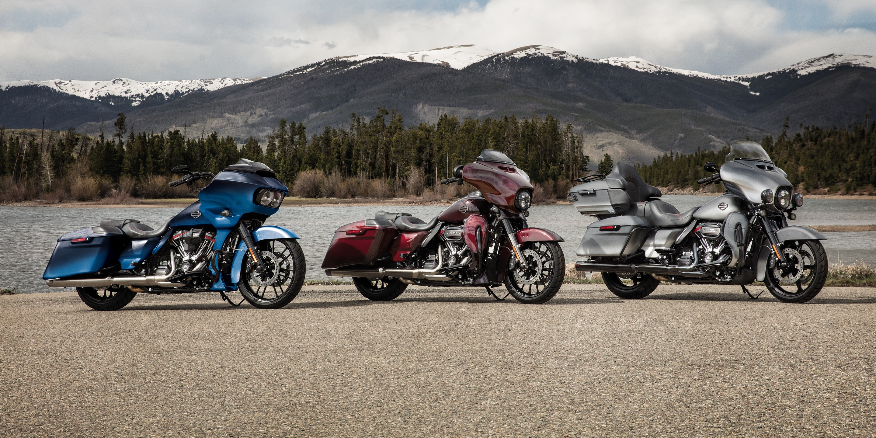 Three CVO Harley-Davidson Motorcycles Parked In Front Of A Mountain Range