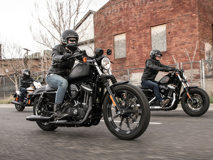 Group of guys riding dark custom Harley-Davidson Motorcycles
