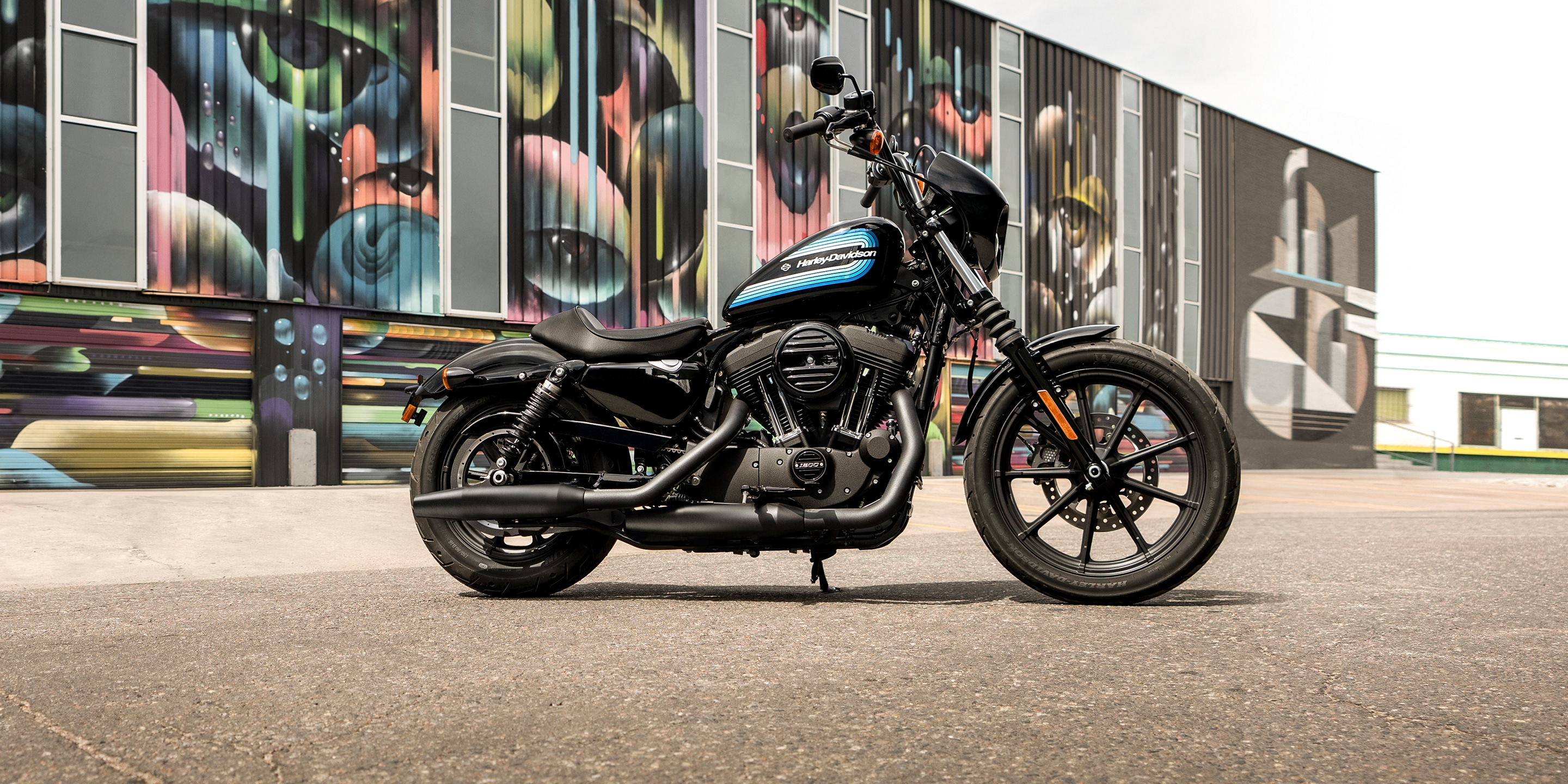 2019 Iron 1200 motorcycle parked in front of a graffiti wall