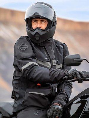 Мотоциклист в черной экипировке Harley рядом с мотоциклом Harley-Davidson Pan America из серии Adventure Touring