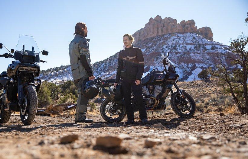 Два мотоциклиста на байках Harley-Davidson Pan America из серии Adventure Touring приветствуют друг друга в пустыне